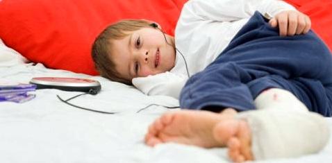 Ein Junge liegt mit Gipsbein im Bett uns hört Musik