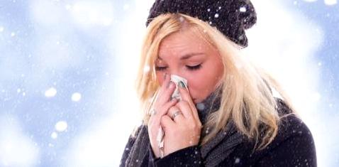 Eine Frau putzt sich im Schnee die Nase
