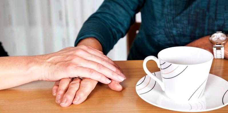 Frau streichelt Hand des Mannes