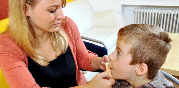 Logopädin hilft einem stotternden Kind